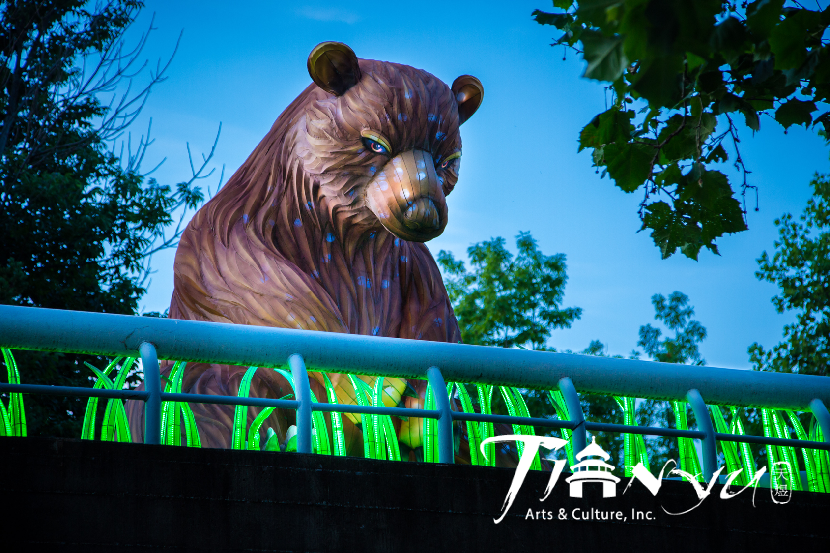 Giant Chinese lantern bear sits in grass.
