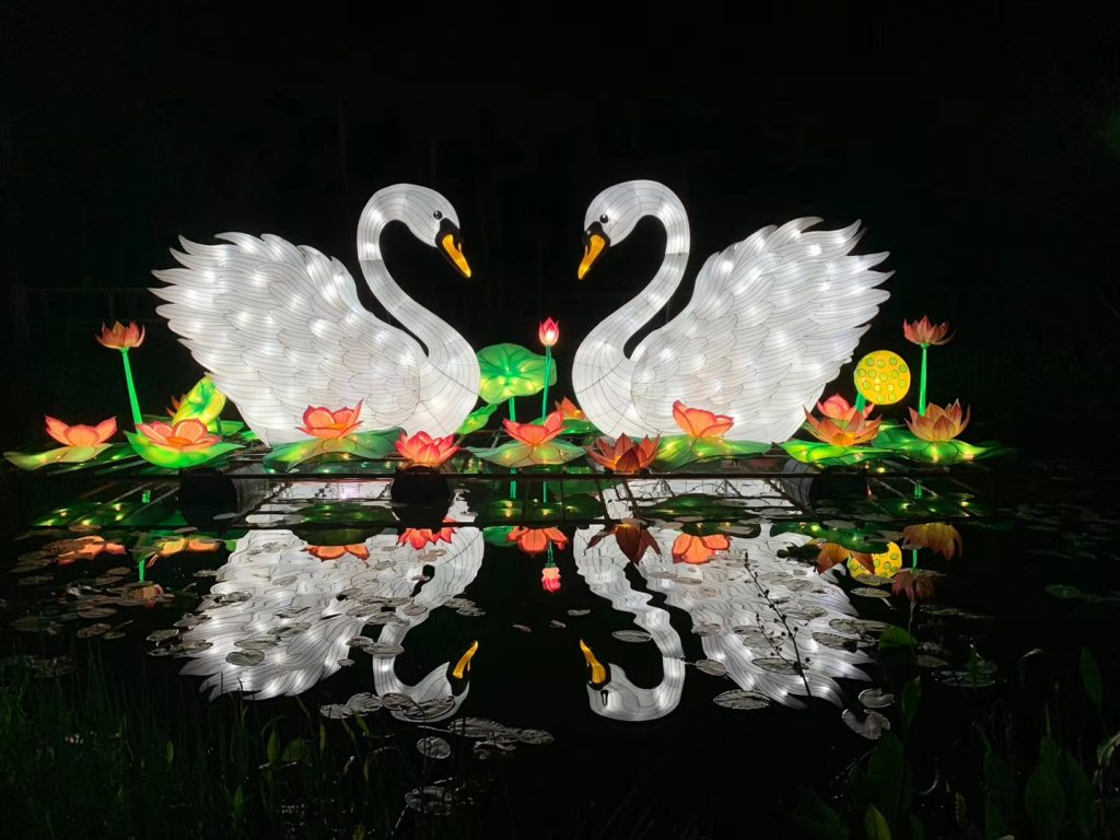 Two 10-foot-tall swan lanterns on the water at the Central Florida Zoo & Botanical Garden festival